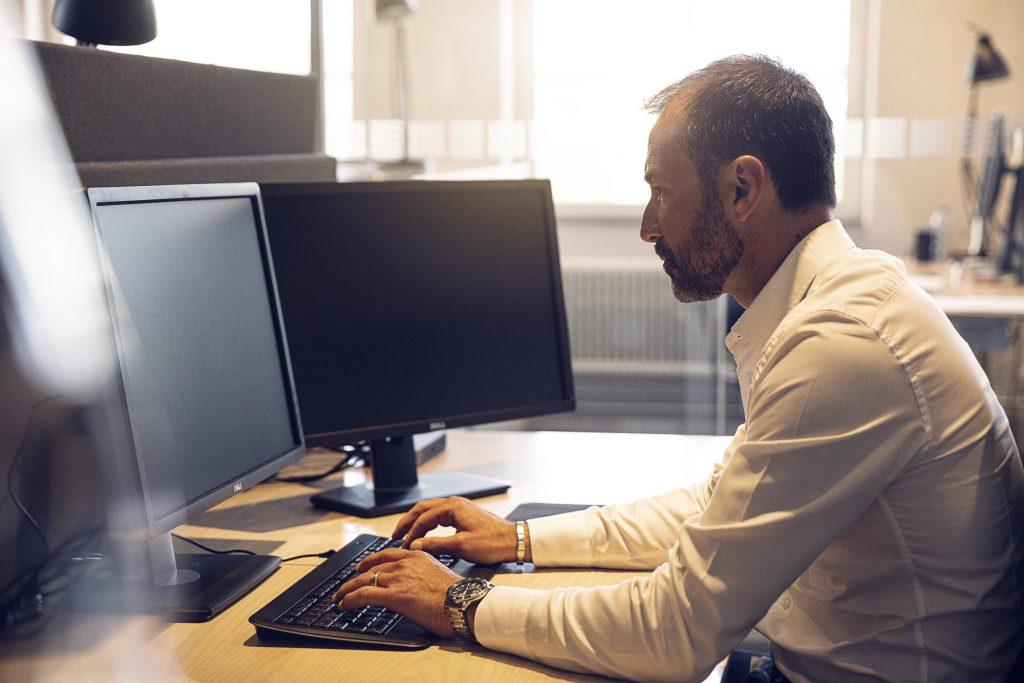 Man som sitter vid dator och administrerar sin fordonsflotta